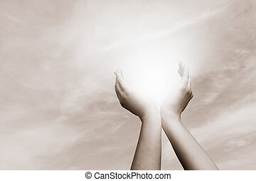 Raised hands catching sun on cloudy sky. Concept of spirituality, wellbeing, positive energy