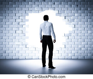 Businessman standing next to a hole in a brick wall. Light coming from outside
