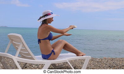 Woman applying sunscreen to her shoulder on a warm near the...