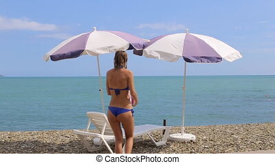 Woman relaxing on caribbean beach with sun umbrellas and beds.