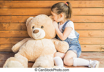 Little girl playing with teddy bear - Outdoor portrait of...