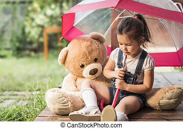 Little girl playing with toy bear - Outdoor portrait of...