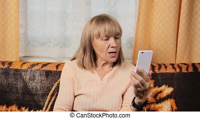 Senior woman video calling on her mobile phone smiling with...