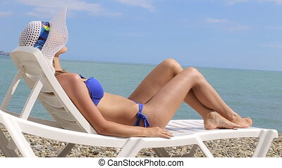 young woman relaxing on tropical beach lying on beach lounger
