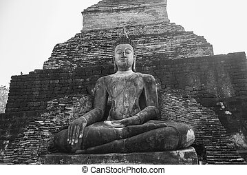 Black and white view of old buddha statue in ancient temple