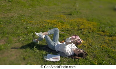 Beautiful Young Woman Laying on The Grass And Listening To...