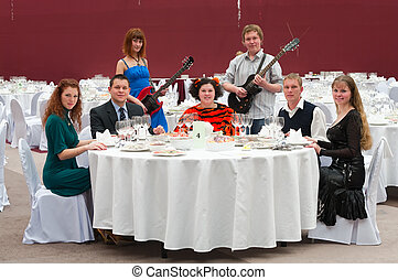 Five young people at round white table in restaurant and two artists with guitars. Dinner party