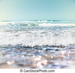 Surf and Bokeh - Ocean waves and surf with bokeh effects in...