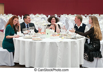 Five young people at round white table in restaurant Dinner...