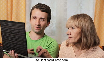 Adult male teaches old woman working for a laptop. Mother and son sitting on a sofa at home