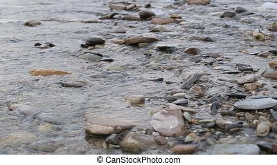 A river flows over rocks in this beautiful scene in the...
