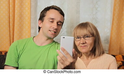 Adult son and elderly mother making video call via telephone...
