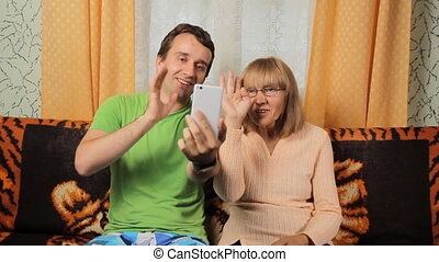 Adult son and elderly mother making video call via telephone. Mother and son smiling at home on sofa