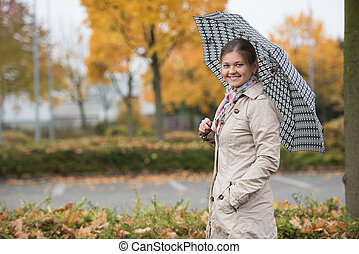 Pretty girl with umbrella - Young woman standing under...