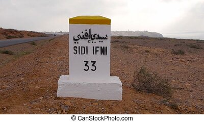 Closeup of distance sign road to Sidi infi written in French...