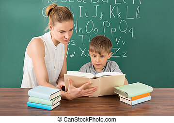 Pupil Reading With Teacher In Classroom