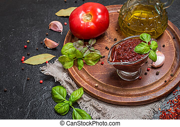 Homemade tomato sauce adjika, herbs and vegetables on a...