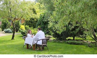 Couple in the white bathrobes have breakfast in the garden.