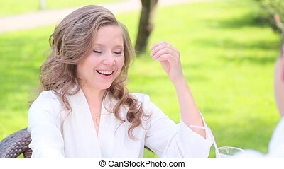 Woman in white bathrobe smiling in the garden