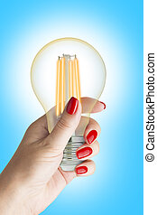 LED filament light bulb in female hand. Isolated on blue...