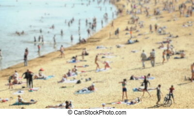 People sunbathing on the crowded sand beach - Blurred beach...
