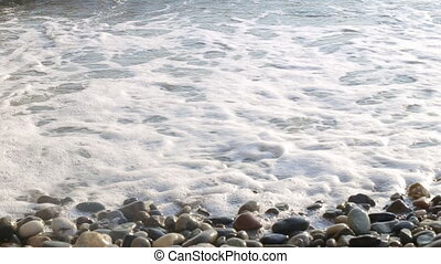 Waves gently wash up onto the beach and recede as the sun is setting.