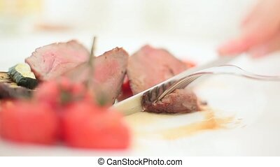 Cutting roasted meat with fork and knife