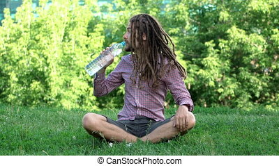 Young man drinking bottle of water with dreadlocks on a...