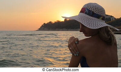 Woman applying sunscreen to her shoulder on a warm near the sparkling sea