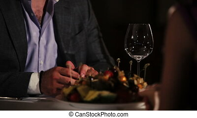 Man in jacket, purple shirt sitting at table in restaurant with woman. Romantic