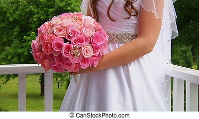 Bride in a designer dress holding a rose bouquet. - White...