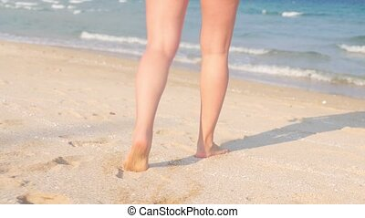 Barefoot legs of caucaisan woman walking on sand into the waving sea water. Dolly in handheld shot