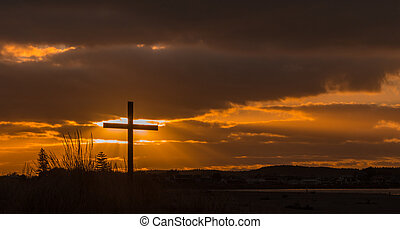 Rays of Salvation - Cross in a hill with the sun behind the...