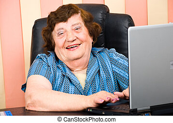 Happy elderly business woman using laptop in office