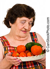 Elderly woman holding a plate wth tomatoes and cucumbers