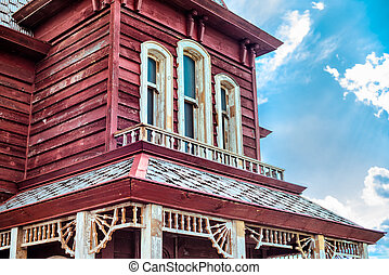 Old american western red house against blue sky