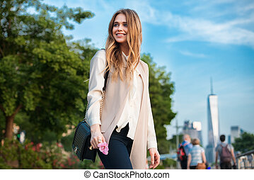 happy young woman walking in park