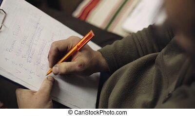 Man sit and underline words in list on sheet of paper in...