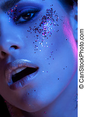 High end beauty image of girl covered in glitter in blue...