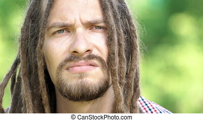 portrait of dreadlock man on a green background in the park