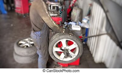 Mechanic balancing car wheel on automated machine checking -...