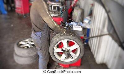 Mechanic balancing car wheel on automated machine checking