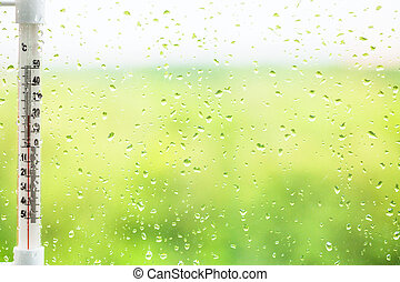 raindrops on window pane and thermometer - green background...
