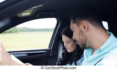 happy couple with map discussing route in car - travel,...