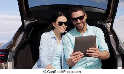 happy couple with tablet pc at hatchback car trunk 36