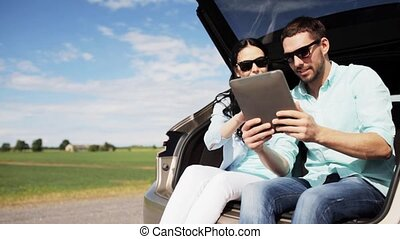 happy couple with tablet pc at hatchback car trunk 23 -...