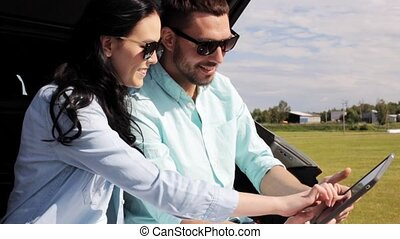 happy couple with tablet pc at hatchback car trunk 34 -...