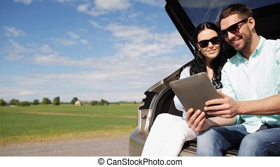 happy couple with tablet pc at hatchback car trunk 21 -...