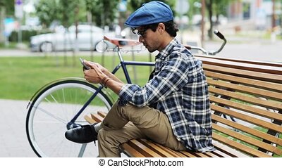 man with tablet pc sitting on city street bench 31 -...