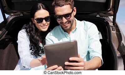 happy couple with tablet pc at hatchback car trunk 32